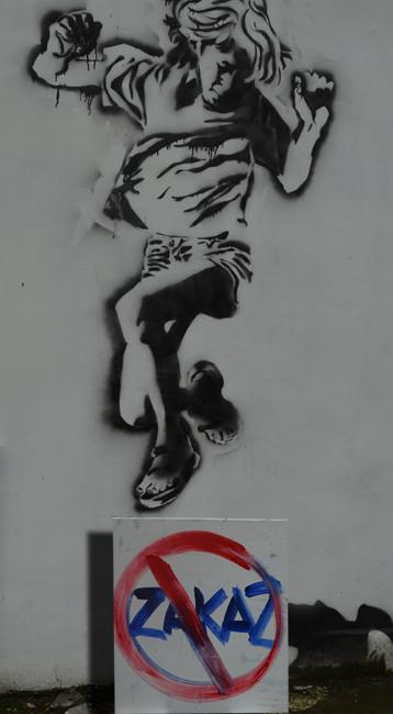 XY zakaz zakazywania na tle fragmentu muralu